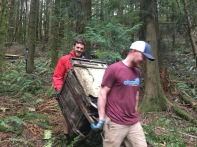 Ike and John carrying an old dishwasher off the hill.